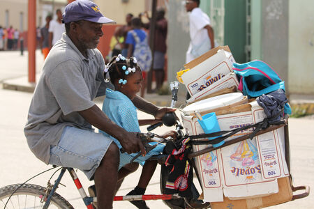 jamaican ethnicity: FALMOUTH, JAMAICA � MAY 11: An unidentified man with daughter riding bicycle outside the port of Falmouth on MAY 11, 2011 in Jamaica ahead of the national labour day celebrations. Editorial