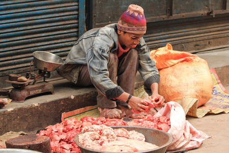 New Delhi, India, February 25, 2012  A street market with a butcher preparing and cutting meat in New Delhi, National Capital Region, North India