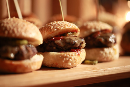 Hamburger sliders  on a rustic cutting wooden board. Stock Photo