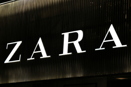 synonymous: SYDNEY, AUSTRALIA – SEPTEMBER 13, 2014: Zara illuminated sign at night in Sydney's CBD shopping district, an area synonymous with luxury shopping brands. Editorial
