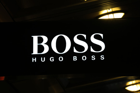 synonymous: SYDNEY, AUSTRALIA – SEPTEMBER 13, 2014: Hugo Boss illuminated sign at night in Sydney's CBD shopping district, an area synonymous with luxury shopping brands.
