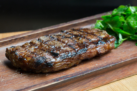 new york strip: Char-Grilled Steak served on Wooden Board