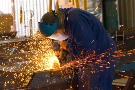 Sparks fly from a grinder in an industrial steel welding workshop. photo