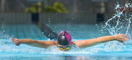 thrust: Swimming butterfly in a olympic swimming pool. Training for a swimming carnival