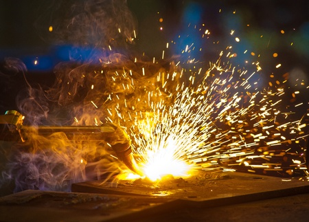 A tradesman boilermaker using oxy equipment in a steel welding works. Sparks, flames and smoke come from an oxy cutting torch in a steel fabrication welding factory which is part of a coal mine.