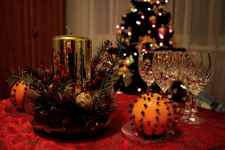 Christmas Eve. Close up of decorated candle, empty vine glass and orange fruit with gillyflower. Christmas tree is in the background