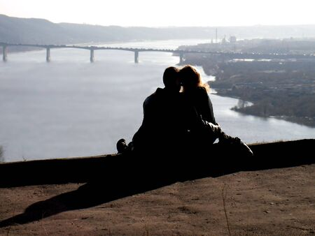 Amorous pair at a rock above a river. A time stoped. Even cars put up on the bridge photo