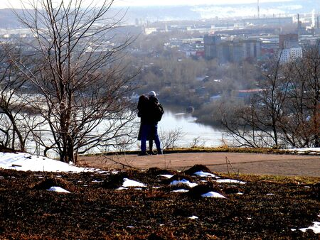 Kissing couple above spring river and town photo