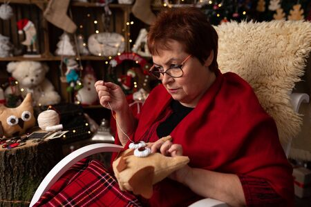 Grandmother sews a plush owl in Christmas arrangement Stock Photo