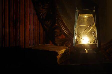 oil lamp: Book, oil lamp and mirror in the dark