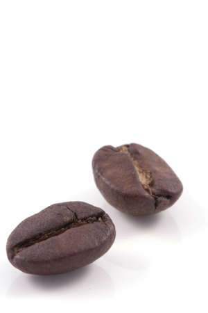 coffe break: close up of two dark roasted fair trade coffee beans isolated on a white background Stock Photo