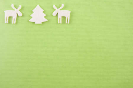 two white felt reindeers next to a white felt christmas in the left upper corner on a bright green paper background Stock Photo - 8292362