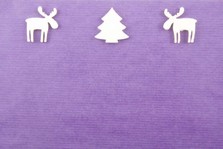 two white felt reindeers next to a white vilt christmas in the left upper corner on a deep purple paper background Stock Photo - 8292384