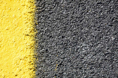 urban road: close up of a dark grey asphalt road divided by yellow paint Stock Photo