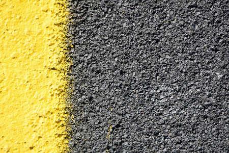 road texture: ravvicinata di un asfalto grigio scuro suddiviso per vernice gialla