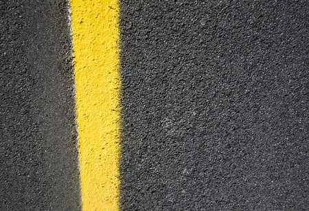 close up of a dark grey asphalt road divided by yellow paint photo