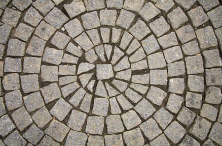 Old grey pavement of cobble stones in a circle pattern in an old medieval european town. photo