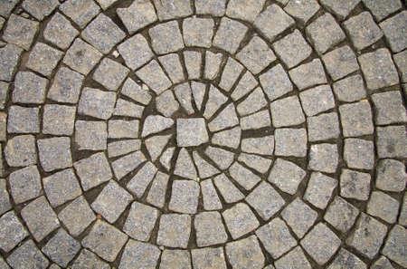 cobble: Vecchia pavimentazione grigia di cobble pietre in un pattern di cerchio in un centro storico medievale di europeo. Archivio Fotografico