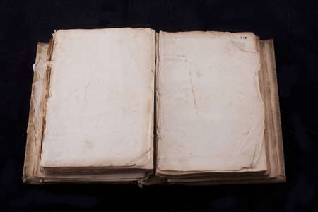 ancient book, almost 300 years, opened on two blank sheets isolated on black photo