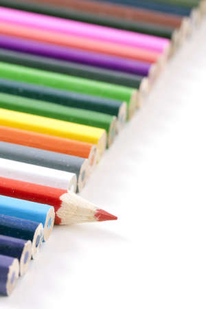 colorfull pencils with a small depth of field, diagonal line with a red pencil different than the other colored pencils on white with copy space. Stock Photo - 8860144