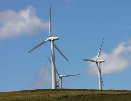 enviromental: Wind Farm Turbines against blue sky with white clouds  Stock Photo