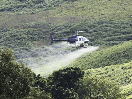 Crop sprayer duster helicopter, spraying mountains, fields and land photo