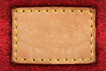 leather label: Blank yellow leather label on red carpet background
