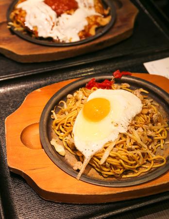 yakisoba: Yakisoba on Hot Plate with Fried Egg on Top Stock Photo