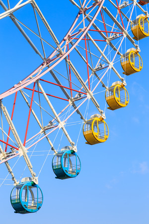 round rods: Ferris wheel with colorful baskets on blue sky background (nobody)