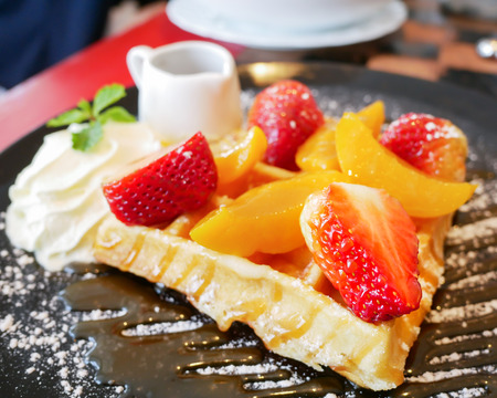 Closeup honey waffle with strawberry and peach and icing sprinkle on black plate (soft focus) Archivio Fotografico