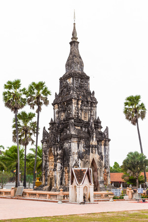 Savannakhet Laos-December 28 2018 :  Travel attraction at That Ing Hang, Ancient herritage of old pagoda in temple with palm trees on white background (Editorial image)