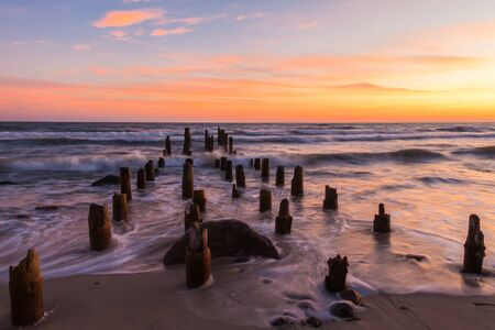 breakwaters: Wooden breakwaters into the sea at dawn Stock Photo