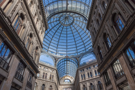 surmounted: NAPLES, ITALY ? OCTOBER 01, 2013: Interior of Galleria Umberto I, a public shopping gallery in Naples. It was built between 1887?1891. It is a high and spacious cross-shaped affair surmounted by a glass dome braced by 16 metal ribs