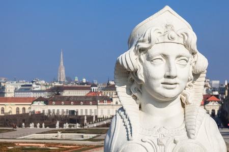 WIEN, AUSTRIA, MARCH 9, 2014: Rococo Sphinx in the Belvedere gardens. In the background - top view of Vienna