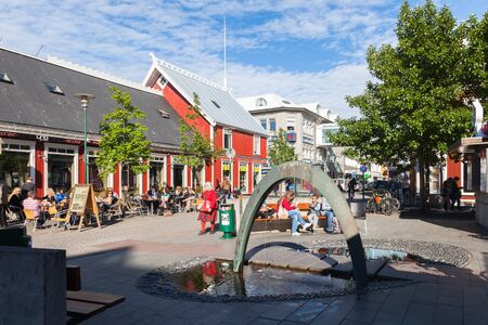 Reykjavik: REYKJAVIK, ICELAND -JUNE 27, 2014:  Square in Reykjavik with a fountain and outdoor cafes. Many tourists have a rest