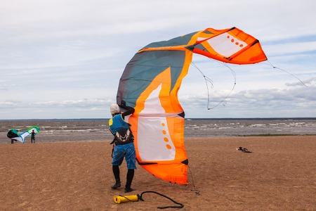 kite surfing: Kite surfer wearing a wetsuit is preparing his kite on a windy cold day