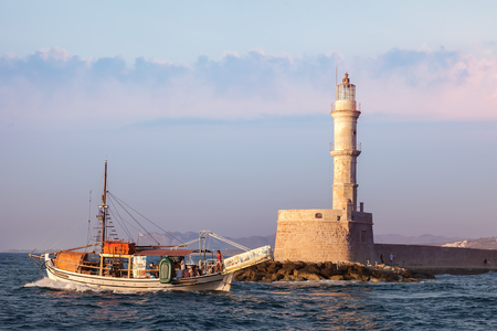 surviving: CRETE,  GREECE - JULY 22, 2015:  Famous lighthouse in Chania and pleasure boat. It is one of the oldest surviving lighthouse in the world Editorial