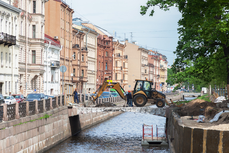 outside machines: AINT PETERSBURG, RUSSIA - MAY 25, 2016: Repair of the bridge on the New Holland Island in downtown St. Petersburg. Works excavator and male workers Editorial