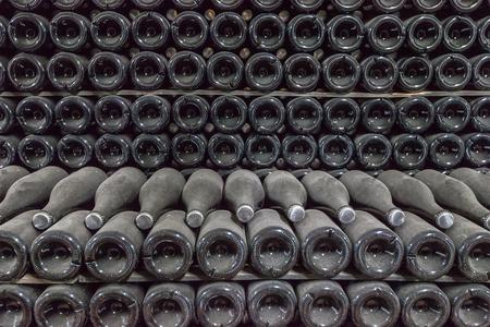 bottoms: Bottoms of wine bottles. Background dark and textured