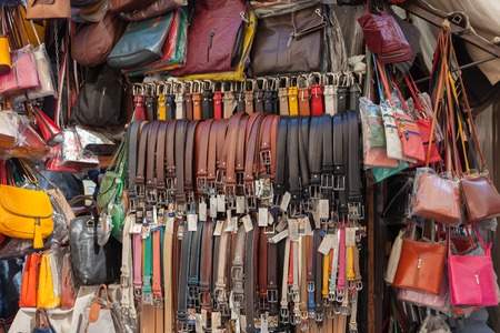 Florence, Italy – April 10, 2017: Belts, bags and other leather goods in the street market in the center of Florence