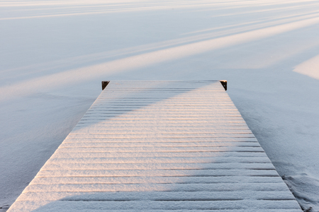 Small wooden pier covered with snow, winter lake