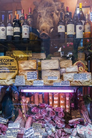 Orvieto, Italy – March 24, 2018: Shop window with bottles of wine, cheese, smoked sausage, meat Editorial