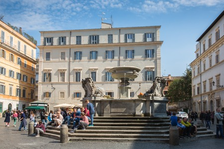 Rome, Italy – March 27, 2018: Tourists rest near the fountain in the center of Rome