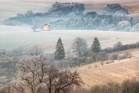 Winter rural landscape with frosted wavy fields, trees in hoarfrost and old windmill on hill. Moravia, Czech Republic.