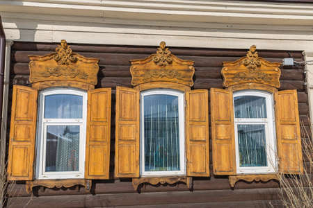 Window with the wooden carved architrave in the old wooden house in the old town Ulan-Ude