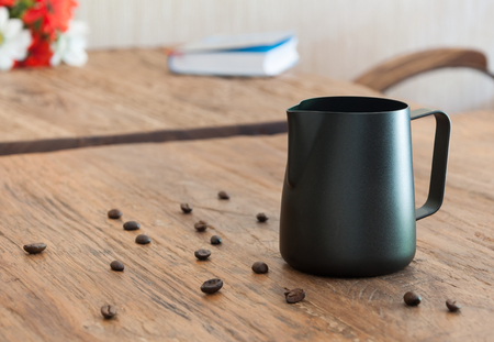 wood table: Black milk pitcher on wood table Stock Photo