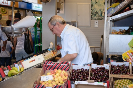 MALAGA, SPAIN - JUNE 10: An unidentified seller packs the fruit at his shop in the popular central market on June 10, 2011 in Malaga, Spain.It was renovated in 2010 and it was reopened on March 2011.