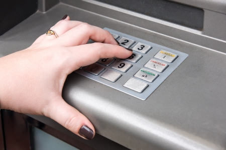 womans hand entering PIN code on ATM machine photo