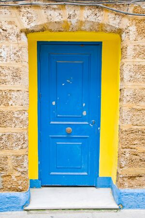 blue and yellow wood door in Cadiz in Andalucia, Spain photo