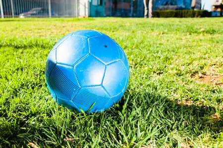 champ vert: Ballon de football bleu sur fond vert